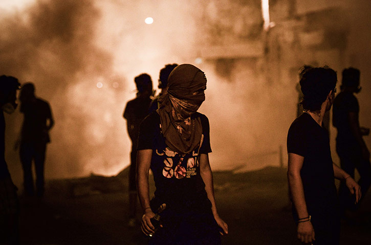 A Bahraini protestor holds a Molotov cocktail during clashes with police