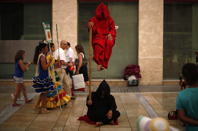 Women in traditional Sevillana dresses walk by street performers in Malaga
